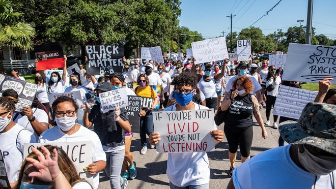 Protesters march Saturday toward the Caldwell County Justice Center in Lockhart during a demonstration against police violence and racism. The protest was also motivated by calls to remove a Confederate monument outside the Caldwell County Courthouse, which was installed in 1923.