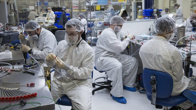 Employees work in a clean room at Dynamic Manufacturing Solutions in Austin in this file photo. A new report from the Federal Reserve Bank of Dallas indicates manufacturing activity has rebounded in June from a pandemic-induced downturn over the previous three months.