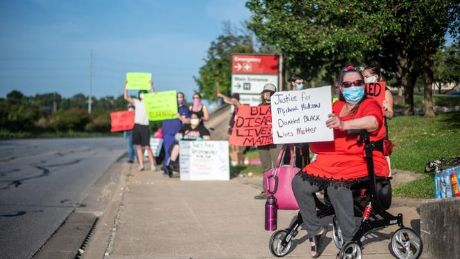 Robin Hoffpauir holds up a sign at a protest for Michael Hickson, who died of COVID-19. Protesters outside of St. David's South Austin Medical Center on Saturday allege that the hospital may have rationed care to Hickson because he was disabled.