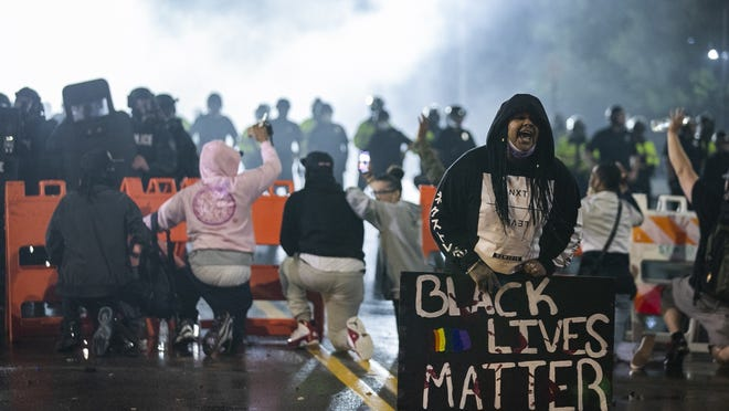 """A woman yells """"Black Lives Matter,"""" and """"I Can't Breathe,"""" as demonstrators kneel in front of the police barricade outside the Brockton Police Station on Commercial Street on Tuesday, June 2, 2020."""