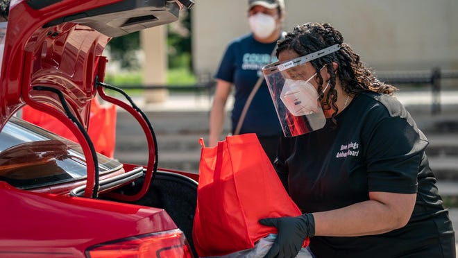 A volunteer loads school supplies and supplies to prevent the spread of the coronavirus, including masks and hand sanitizer, into a car at Mendez Middle School in Southeast Austin on Aug. 8.
