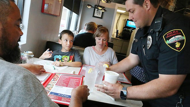 Raymond Drye, Grant Drye, 8, and Angela Drye get special service from Cpl. John Clukey, Jacksonville Police Department Service Officer, as folks dining at the Kettle Diner Thursday were served by JPD's finest -- all to benefit the N.C. Special Olympics Torch Run. The officers served guests from 9 a.m. to 2 p.m. with all tips going to Special Olympics athletes.