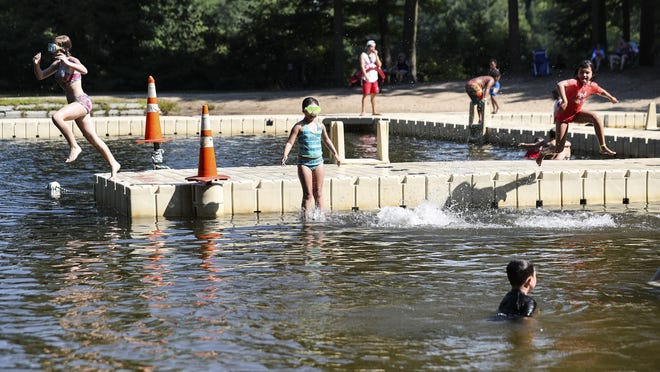 Children cool off at Island Grove in Abington recently as temperatures near 100 degrees.