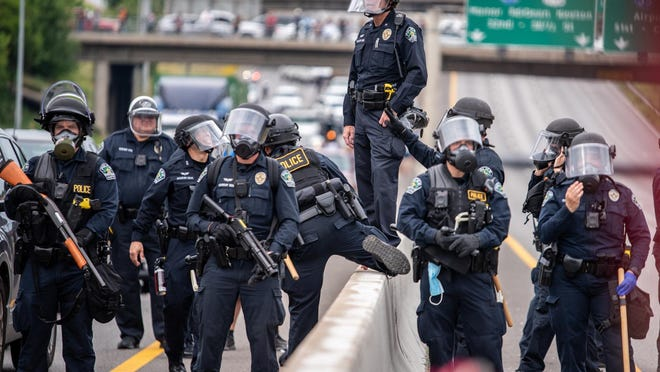 Austin police officers line up along Interstate 35 before using tear gas and clearing the area during a protest in Austin on Sunday.