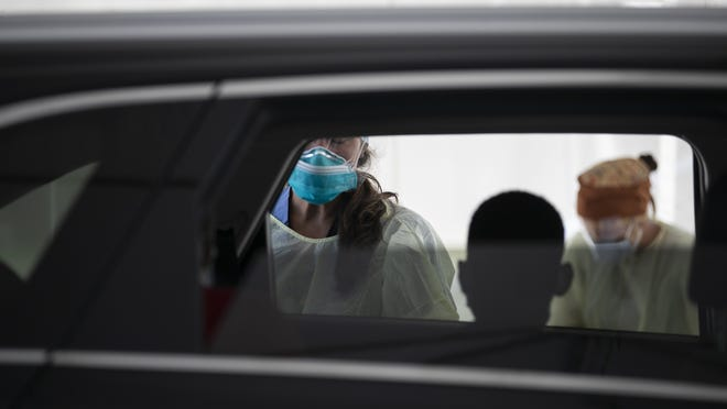 A child is silhouetted before a nurse practitioner tests him at a drive-thru coronavirus testing site.