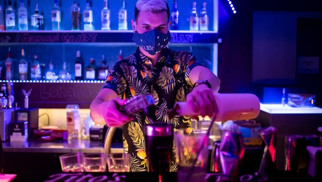 A bartender pours drinks at Highland Lounge in Austin in June, before Gov. Greg Abbott closed bars statewide on June 26. Bars in areas with low COVID-19 hospitalization rates can open at 50% capacity starting next Wednesday -- but only with approval from local officials.
