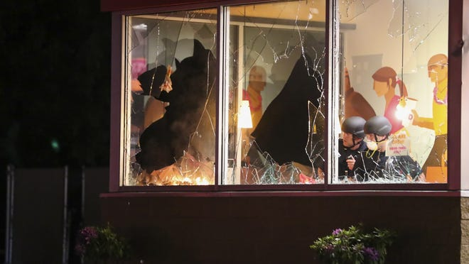 Brockton police try to put out a fire in the Dunkin' Donuts on Montello Street after demonstrators smashed windows and ignited the flames on Tuesday, June 2, 2020.