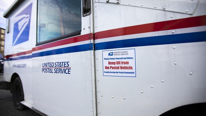 A sticker asking customers to keep a six-foot distance from carriers in an effort to limit the spread of the coronavirus is seen on an United States Postal Service carrier truck on Monday, May 4, 2020.