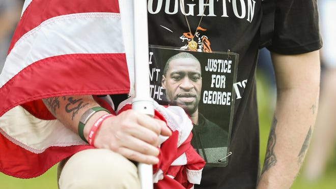 Michael LaFleur holds the American Flag and wears a sign asking for justice for George Floyd to the vigil  in Halloran Park in Stoughton on Wednesday, June 3, 2020. George Floyd was murdered in Minneapolis when a police officer held a knee on his neck for nearly nine minutes.