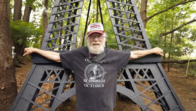 Steve Temple  with the replica of the Eiffel Tower he built in his backyard in Abington.