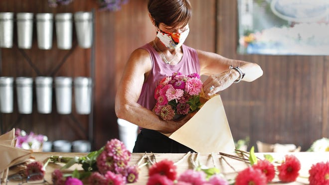 Jan Burkhardt bunches fresh flowers for drive-up customers on Tuesday August 11, 2020. Greg Derr/The Patriot Ledger