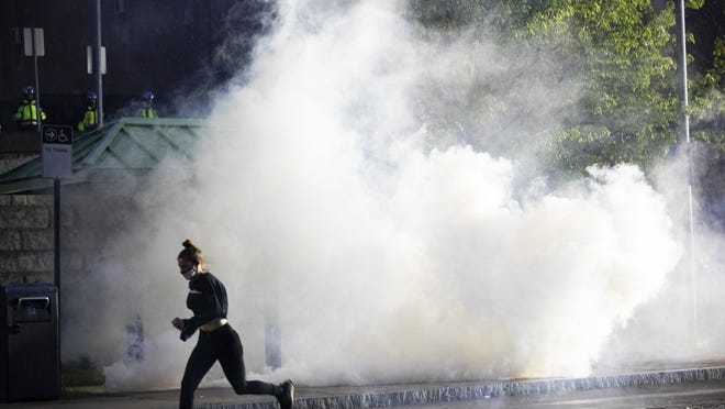 A protester flees down Commercial Street in Brockton from tear gas on Tuesday, June 2, 2020.