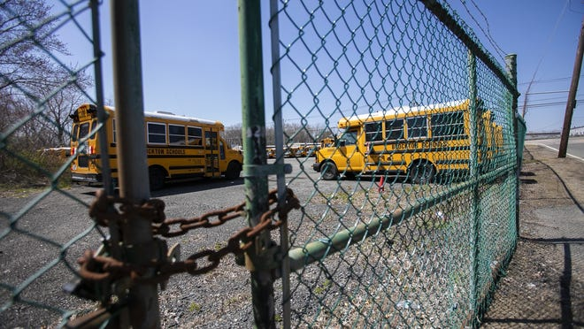 In an April 19, 2020, file photo, Brockton Public School buses sit unused in a lot on Oak Street after schools were closed due to the coronavirus pandemic.