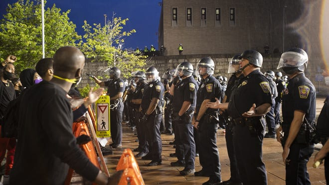 Brockton police officers talk with protesters gathered in front of the Brockton Police Department barriers on Commercial Street during protests on Tuesday, June 2, 2020.