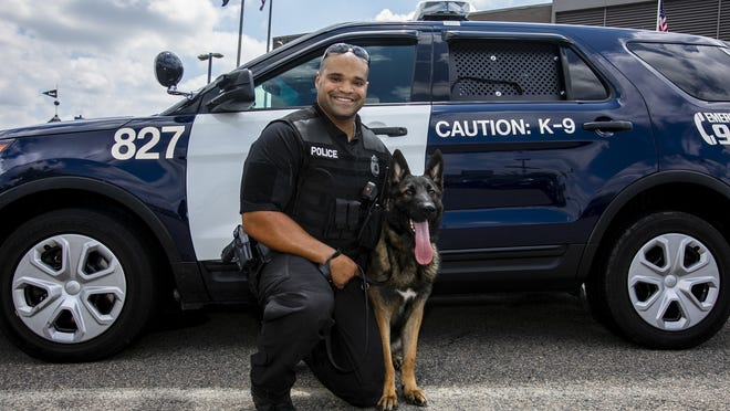 Brockton Police Officer Jonathan Correira, 28, has a new partner, Enzo the German Shepherd as of Friday; Correira poses for a photograph with Enzo outside the Brockton Police Station on Thursday, July 9, 2020. Correira is the first Cape Verdean K9 officer on the force and has wanted to be a K9 officer since one visited his high school in Quincy.