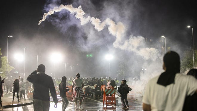 Demonstrators hurl tear gas canisters back at the police as the earlier peaceful protest takes a turn on Tuesday, June 2, 2020. [Alyssa Stone/The Enterprise]