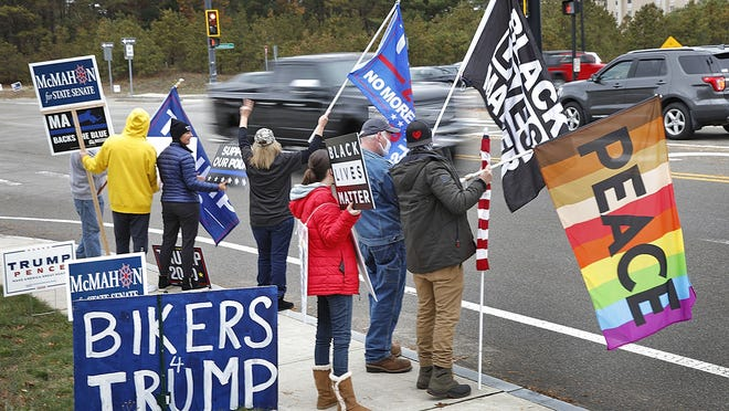 A mix of supporters wave to vehicles on Plympton Road and Commerce Way.  Political supporters stand out in West Plymouth to urge support for their candidates or cause on November 1, 2020  Greg Derr/ The Patriot Ledger