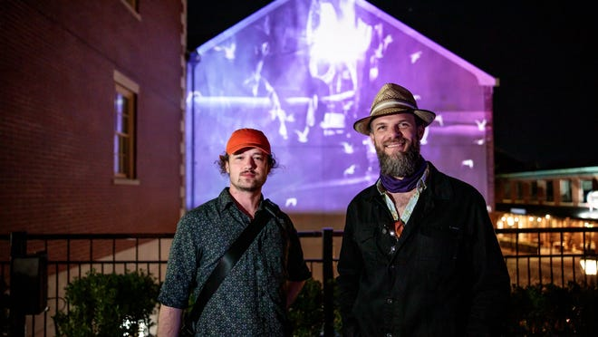"""MASARY Studio co-founders from left, Sam Okerstrom-Lang and Ryan Edwards are seen in front of the art project """"Vessels"""" on view in downtown New Bedford."""