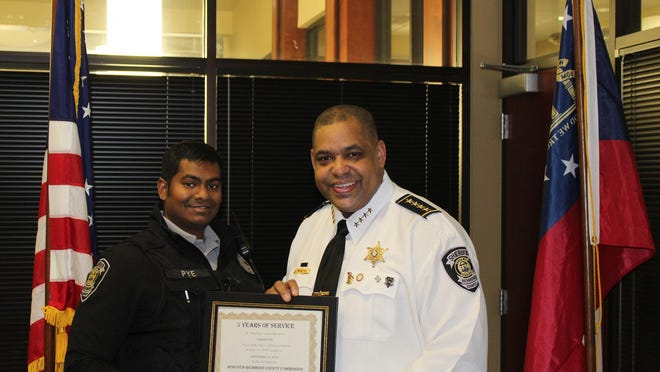 Deputy Caleb Pye, left, with Sheriff Richard Roundtree while being recognized for five years in service with the agency.