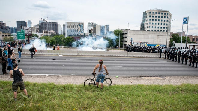 A protester watches as tear gas is used to clear out I35 during a protest in Austin, Texas on May 31.