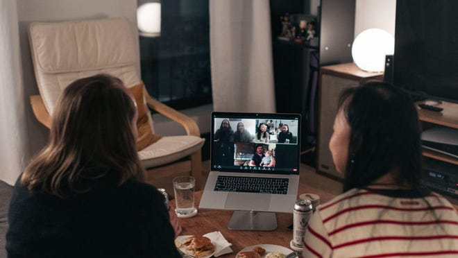 A couple celebrates Thanksgiving with friends by having dinner together over a Zoom video call on November 22, 2020 in New York City. As new COVID-19 cases continue to rise across America, many are forgoing holiday travel and traditional family gatherings out of concern for spreading the virus.