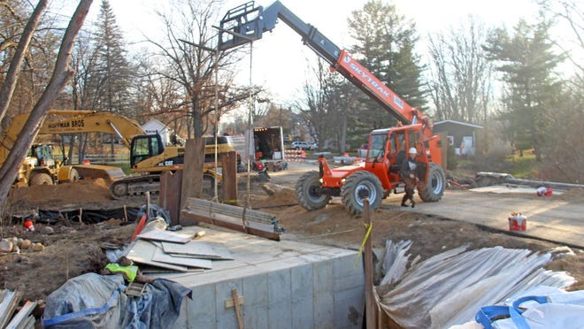 Contractors work to remove concrete forms Thursday morning at the culvert on Fayette Street.