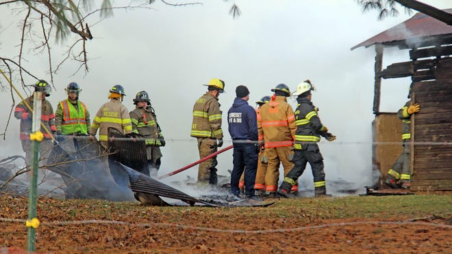 Firefighters from multiple agencies work to extinguish flames and prevent fire from spreading to other nearby structures.
