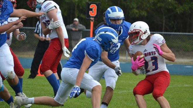 Inland Lakes' Beau Vizina (left) and Ty Thompson (middle) surround a Charleton Heston Academy player during the Bulldogs' season opener in Indian River in September. The Bulldogs have reached the 8-Player Division 1 state semifinals, but their matchup with Suttons Bay is on hold due to a recent announcement from the MHSAA that suspended the remainder of the fall sports postseason for three weeks because of COVID-19 concerns.
