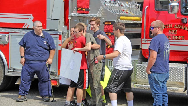 Navy Recruit Kyle Handy is embraced by his girlfriend and North Adams Fire Department firefighters as he leaves for Navy Recruit Training in Illinois Tuesday.