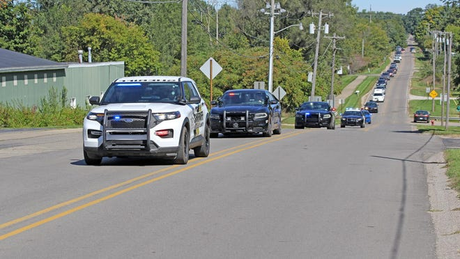 """Law enforcement officers from multiple agencies throughout Hillsdale County led a funeral procession Saturday for retired Hillsdale County Sheriff's Sergeant Richard W. """"Dick"""" Kast."""