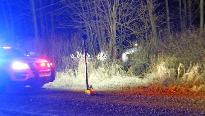 Emergency personnel cautiously navigate the scene of a rollover crash in which power lines were downed after a car struck a power pole, breaking it.