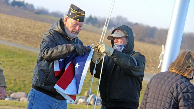 American Legion chaplain Richard Smith assists an airport employee with securing the American flag to the airport's new flagpole Friday morning.