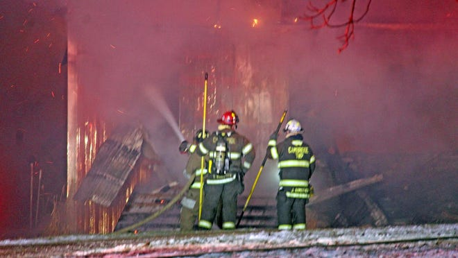 Firefighters work to remove siding from the pole barn in order to extinguish the flames inside.