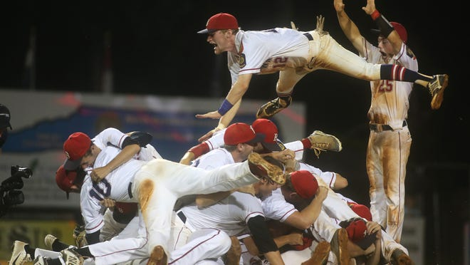Phil Dickinson leaps onto the pile of teammates as Brooklawn celebrates winning the American Legion World Series title.