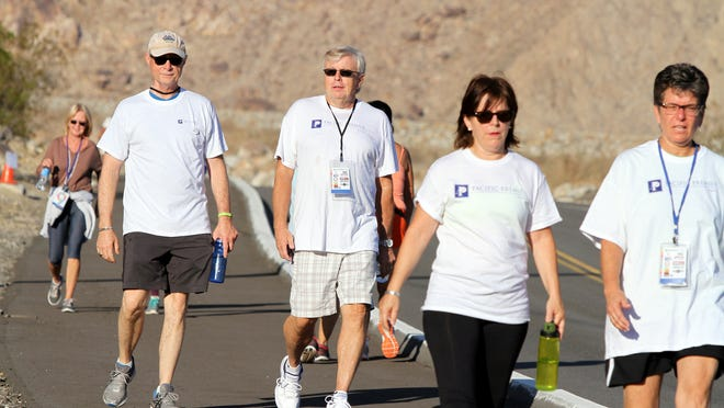 Pacific Premier Bank regional manager Brian Johnston, center, walks down Tramway Road in Palm Springs as part of the eighth in a series of nine weekly United Way walks on Saturday morning, leading up to the 29th annual Tram Road Challenge 6K uphill run and walk.