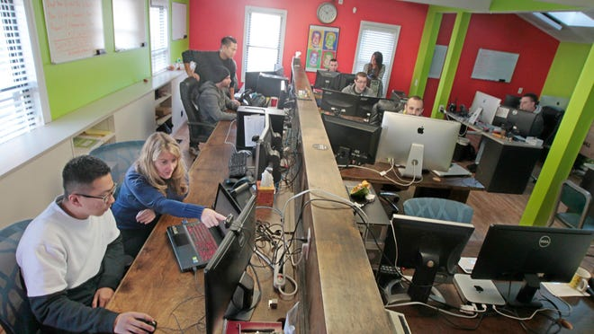 JP Chang, Rochester, graphics designer, bottom left, and Julie Swatling, Pittsford, account manager, second from left, work on a project together in the bright and interactive design workspace at Envative, a web development company, on University Ave. in downtown Rochester Wednesday, Nov. 19, 2014.