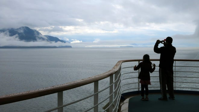 A cruise ship passenger takes photos of Alaska's Inside Passage. The ship stopped in ports including Juneau, Skagway and Ketchikan.