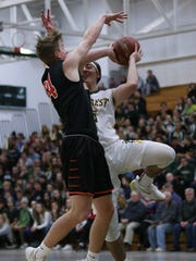 Marshfield's Grant Urban, left, attempts to block a shot by D.C. Everest's Alec Stuedemann during the first half of Friday's Wisconsin Valley Conference boys basketball game.