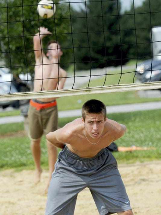 Central York High School graduate Landon Shorts, front, waits at the net during some sand volleyball fun Monday at Cousler Park in West Manchester Township. Shorts returned 12 hours earlier from Iowa, where he competed at an international boys' volleyball tournament.