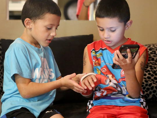 Six-year-old Kysun Melendez, left, checks to see if he signed his brother's, 7-year-old Zayden Melendez, cast at their grandmother's home on Sept. 7.