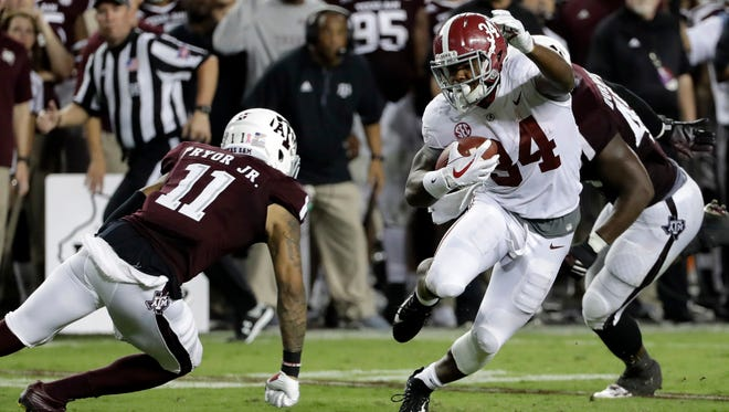 Alabama's Damien Harris (34) eludes Texas A&M's Larry Pryor (11) as he rushes for a first down during the second quarter of an NCAA college football game Saturday, Oct. 7, 2017, in College Station, Texas. (AP Photo/David J. Phillip)
