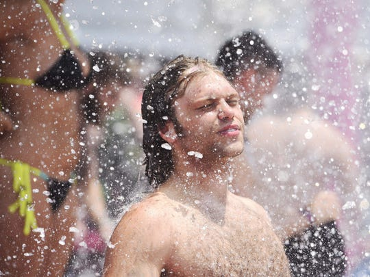 Viktor Pulaski of Grand Rapids, Mich., cools down in the fountain on day four of the Bonnaroo Music & Arts Festival on June 12, 2016.