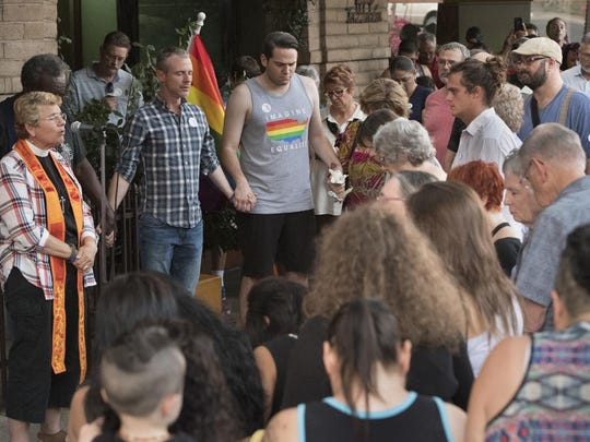 Rev. Suzy Ward, left, and The Source LBGT Center Executive Director Brian Poth lead about 150 people gathered Sunday, June 12, 2016 in Downtown Visalia on Main St. in a candlelight vigil to honor those killed and injured during a shooting early Sunday's shooting in Orlando, Fla.