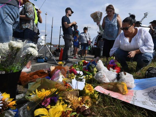 Brenda Woldridge, second from left, and Meredith Cooper lay flowers at a memorial outside the First Baptist Church, after a mass shooting that killed 26 people in Sutherland Springs, Texas on Nov. 7, 2017.