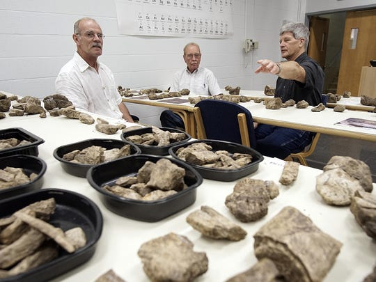 Nigel Brush, professor of geology, talks about a find with Clint Walker, owner of the land where they discovered mastodon bones, and Jeff Dilyard, a retired teacher who helped out with the dig, during a presentation at Ashland University's Kettering Science Building.