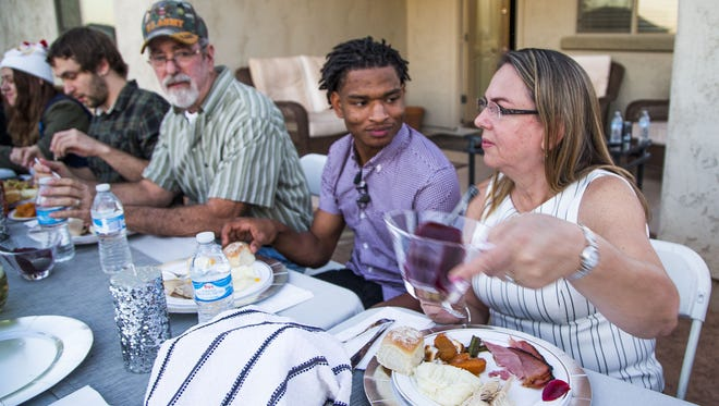 """Jamal Hinton (center), 17, and Wanda Dench (right) and her family and friends have Thanksgiving dinner at Wanda's home on Nov. 24, 2016. Hinton was accidentally invited by Dench through a text, but when they discovered the mistake and he asked for a plate anyway, she said, """"Come on over!"""""""