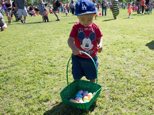 Jacob Lozano,1, looks down at the basket of eggs he with the help of his mother collected at the Egg Hunt for infants and toddlers during Springfest 2017 at Young Park, Saturday, April 15, 2017.