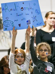 Ava Hughes, left, and Sydney Anderson hold a sign during a rally at Unitarian Universalist Church, Friday, Nov. 20, 2015, in Roanoke, Va., in response to remarks by Roanoke Mayor David Bowers about Syrian refugees. Bowers apologized Friday for invoking the mass detention of Japanese-Americans during World War II in comments about keeping Syrian refugees out of the region.