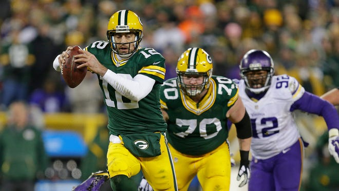 Green Bay Packers quarterback Aaron Rodgers (12) scrambles upfield against the Minnesota Vikings at Lambeau Field.