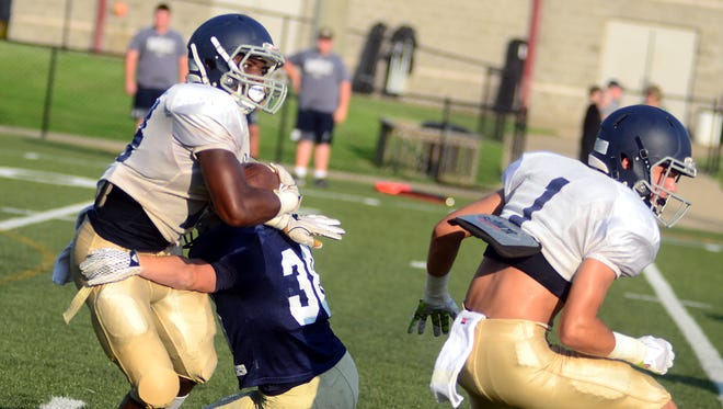 Pope John Paul II High senior C.J. Laws breaks a tackle as classmate Pace Dempsey (1) sets up a block during Friday's scrimmage against Sycamore.